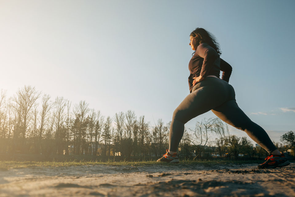 overweight woman stretching on an outdoor run